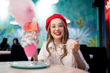 Sweet dessert with pink cotton candy, milkshake and cake. Girl in red beret and glasses, cafe in France