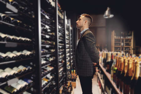 Bartender sommelier picks bottle of wine from rack in restaurant with exquisite drinks 版權商用圖片