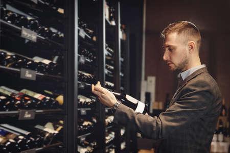 Sommelier Bartender choose wine bottle near rack store restaurant drinks 版權商用圖片