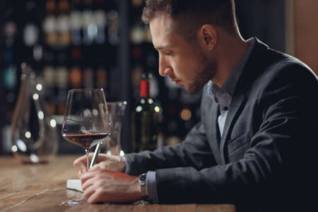 Sommeliers male hold glass red wine tasting degustation card