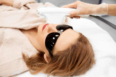 Woman getting face skin care laser treatment in beauty salon
