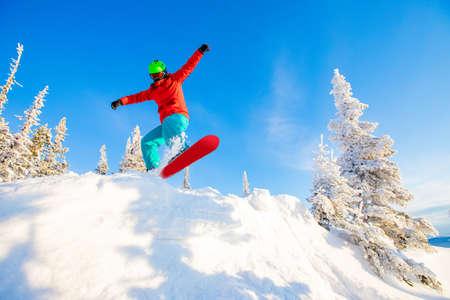 Snowboarder jumps in fresh snow forest. Freeride snowboarding in ski resort