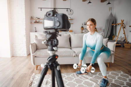 Fitness woman blogger recording video on camera, training home in living room. Concept Lifestyle influencer sport and recreation