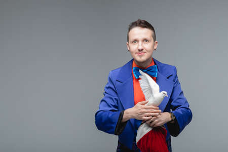 Magician man shows trick with trained white dove bird