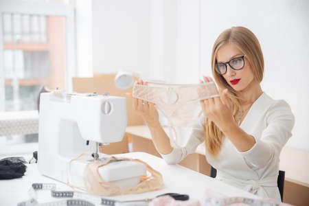 Stylish woman clothes designer works on sewing machine with bra and panties underwear Stock fotó