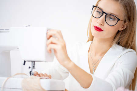 Stylish woman clothes designer works on sewing machine with bra and panties underwear