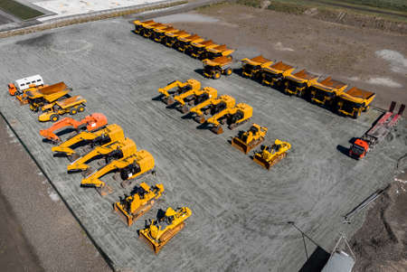 Concept sale of industrial equipment. Parking with big yellow mining truck, bulldozers for coal industry, iron ore and gold. Aerial top view