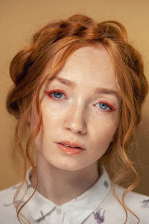 Portrait of red haired young woman with extended colored eyelashes, freckles. Natural beauty concept