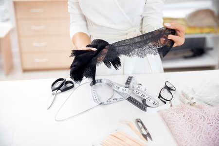 Step 1 process of sewing underwear and clothes, woman tailor cuts blanks for panties from black lace