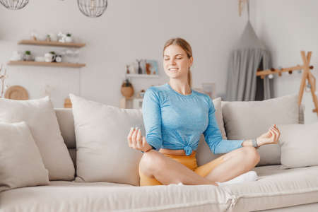 Young woman in sportswear meditates and rests in lotus position on sofa at home after training