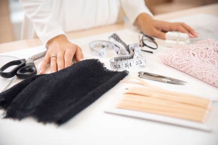 Step 1 process of sewing underwear and clothes, woman tailor cuts blanks for panties from black lace Stock fotó