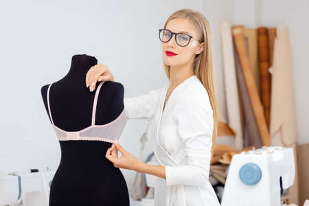 Fashionable business sewing underwear, tailor seamstress woman tries on bra on mannequin