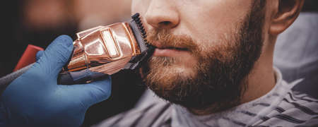 Barber with medical gloves protection pandemic shearing beard to man in barbershop