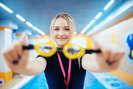 Young woman trainer swimming coach in pool water for children and adults