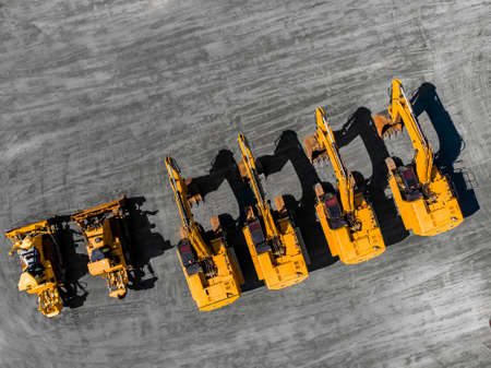 Sale of specialized equipment for mining coal, iron ore and gold. Yellow excavators and bulldozers stand in parking lot. Aerial top view