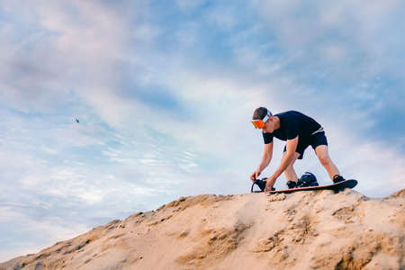Snowboarder climbs to top of sand dune for snowboarding