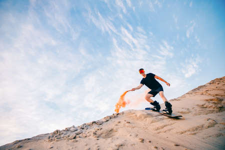 Extreme descent sand on snowboard in desert. Male snowboarder on dunes