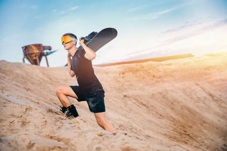 Man sand boarder standing on top with snowboard before extreme downhill