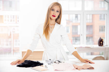 Woman fashion designer clothes in workplace with different lace on table