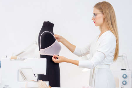 Fashionable business tailor underwear, seamstress woman tries on bra on mannequin