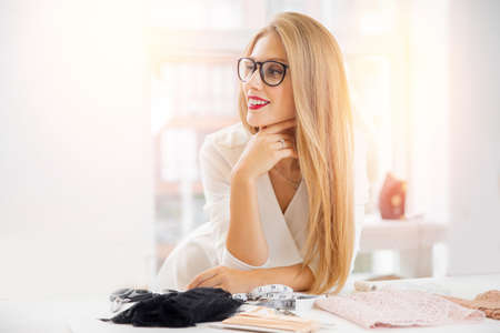 Fashionable business seamstress, portrait of happy woman tailor workplace sews
