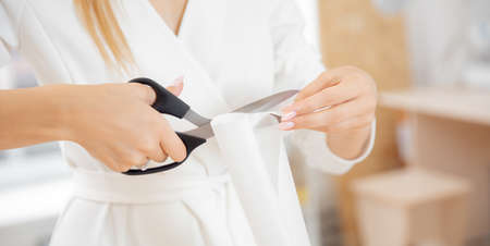 Banner seamstress tailor woman cuts pattern with scissors Stock fotó