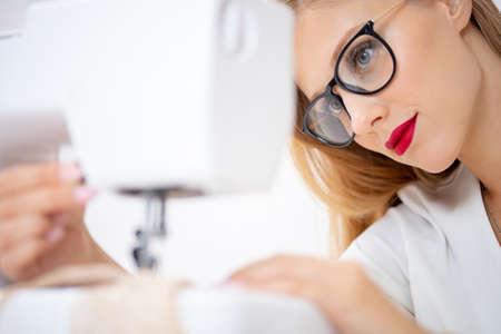 Young fashion designer of women underwear works sewing machine Stock fotó