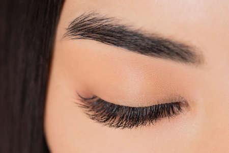 Eyelash extension procedure. Beautiful female asian eyes with long lashes closeup