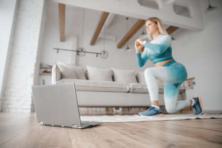 Woman watching video working on laptop computer. Concept Online training fitness workout at home