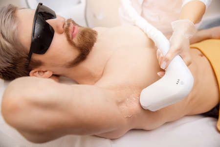 Hair removal procedure from men armpit, laser epilation studio, top view.