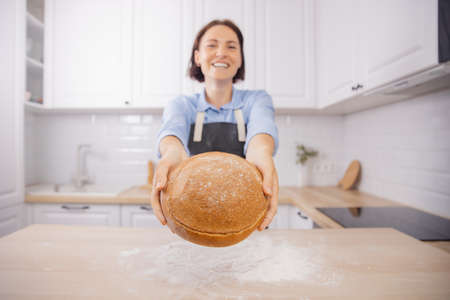 Woman baker in apron holds round bread in hands on background of white kitchen in Scandinavian style