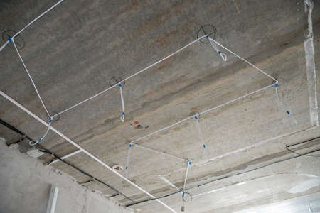 Electrical work with rough finish, electrician connects and mounts copper wires for spotlights on kitchen ceiling