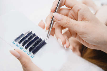 Woman master making fake long lash Eyelash extension procedure 写真素材