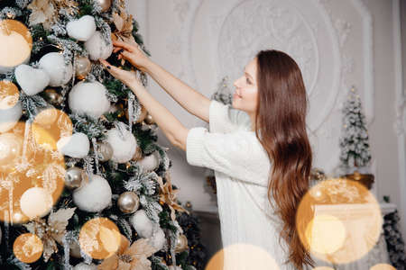 Beautiful caucasian young woman in white warm sweater decorates Christmas tree with balls in living room, bokeh background 写真素材