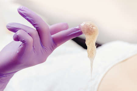 Woman underarm shugaring paste hair removal procedure beauty salon. Epilation concept 写真素材
