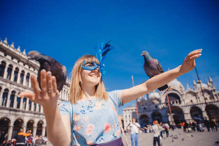Portrait smiling young woman in Venice, Italy in Venetian mask feeds pigeons on St Mark Square. Concept travel 写真素材