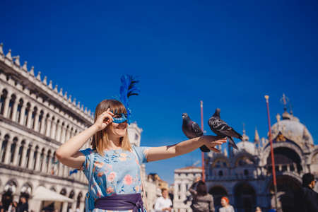 Portrait smiling young woman in Venice, Italy in Venetian mask holding pigeons on St Mark Square. Concept travel