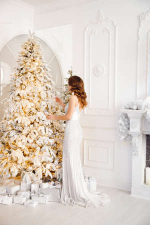Beautiful woman decorates tree white balls and toys. Concept Merry christmas and happy holidays. Bright interior room home 写真素材