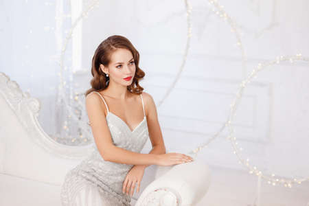 Retro young woman with red lips and wave hairstyle sitting in silver dress on sofa, getting ready for Christmas dancing party