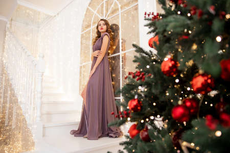 Beautiful girl happy and smiling in evening dress with make-up and hairdo decorates Christmas tree red balls