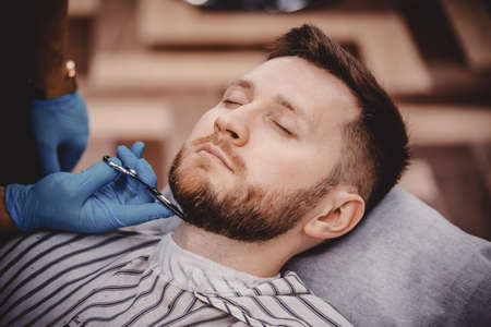 Close-up of barber with medical gloves shearing beard to man in barbershop. Haircut pandemic protection