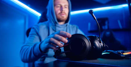 Streamer man cyber esports prepares for online video game, puts on headphones, neon blue 写真素材