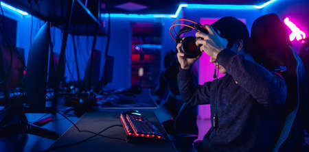 Streamer young man rejoices in victory professional gamer playing online games computer with headphones, neon color 写真素材