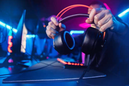 Gaming headphones with a microphone for streaming and online video games in the hands of a man, neon color