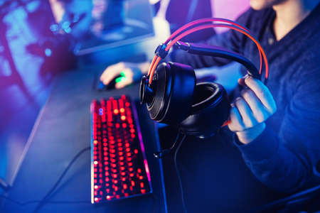 Gaming headphones with microphone and keyboard for streaming online video games in hands of man, neon color