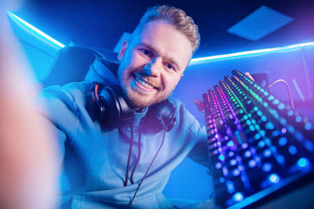 Professional gamer man smile making selfie photo and playing tournaments online video games computer with headphones