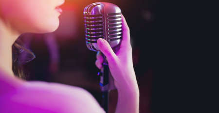 Woman vocalist holds in hand old retro microphone on dark background banner