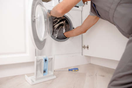 Working man in medical mask plumber repairs fix washing machine in kitchen. Concept service technician