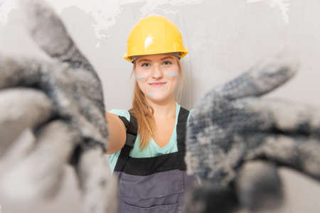 Builder woman in yellow helmet on background of gray wall, face in plaster 写真素材