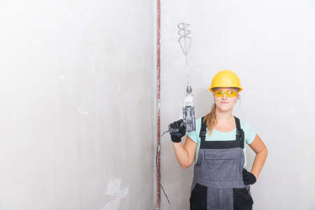 Woman worker makes repairs in apartment, dressed in uniform. Builder Holds mixer for mixing plaster mortar